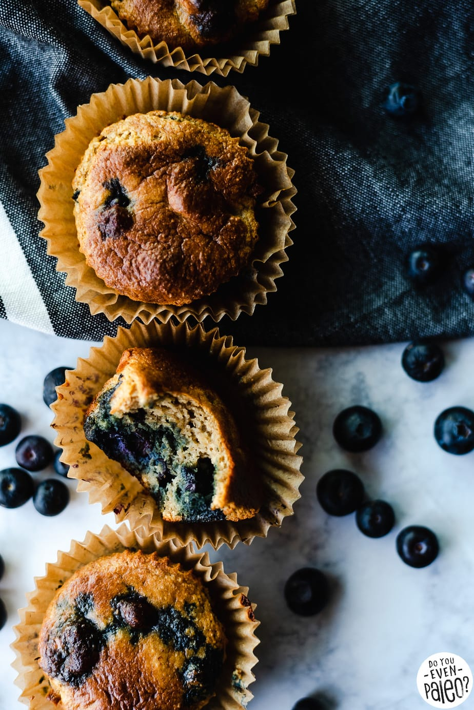 Picture for paleo blueberry protein muffin recipe with four muffins, linens, and scattered blueberries.