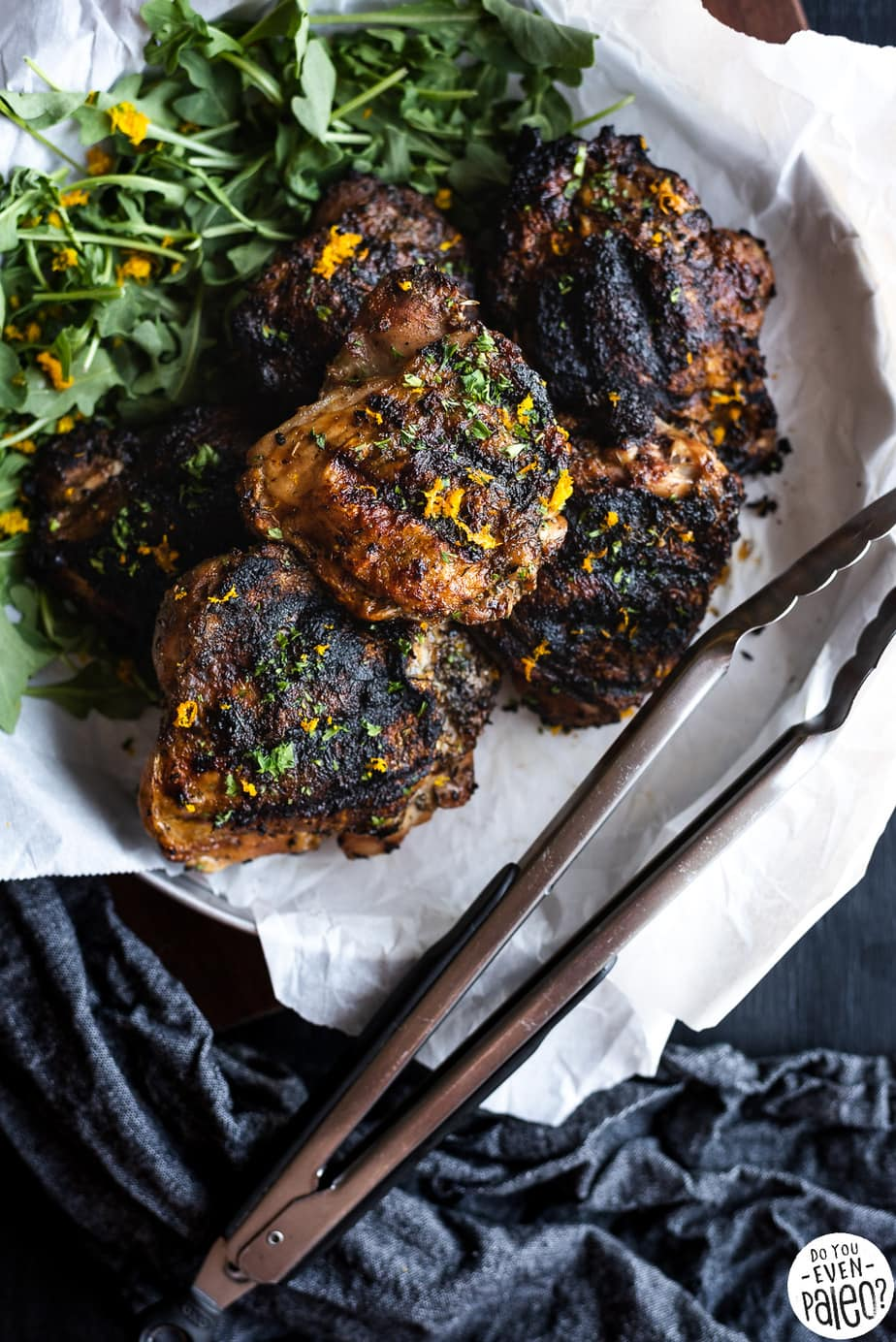 Greek-Rubbed Grilled Chicken Thighs with greens on a tray.