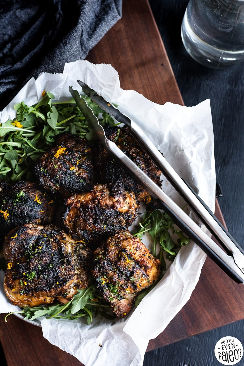 Greek-Rubbed Grilled Chicken Thighs with greens and kitchen tongs on a tray