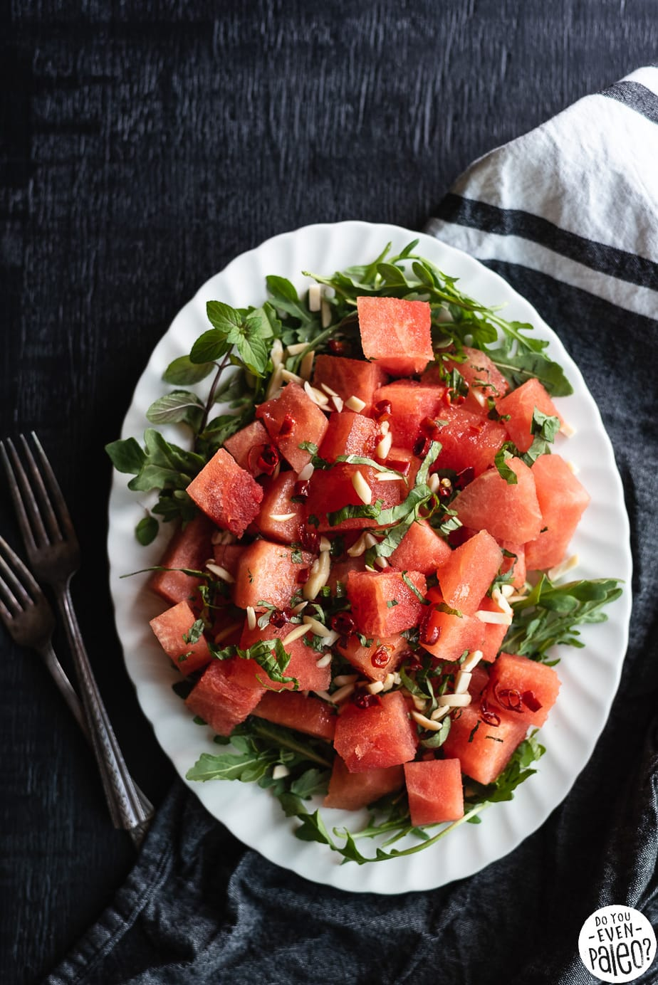 Watermelon Arugula Salad on a white oval plate and dark background
