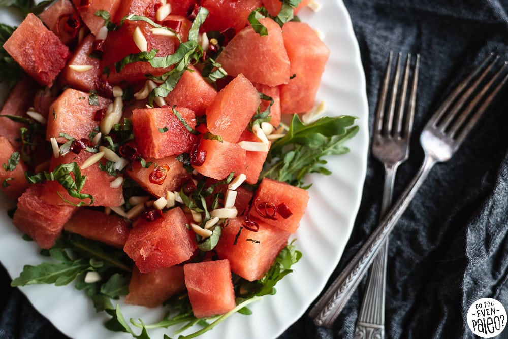 Watermelon Arugula Salad garnished with herbs and almonds on a white plate with two forks to the right.
