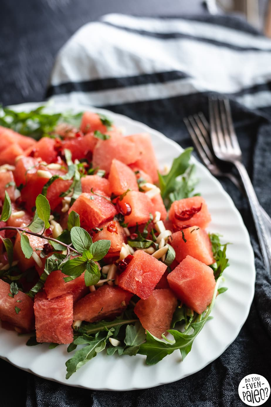 Watermelon Arugula Salad garnished with fresh herbs and almonds on a white plate.
