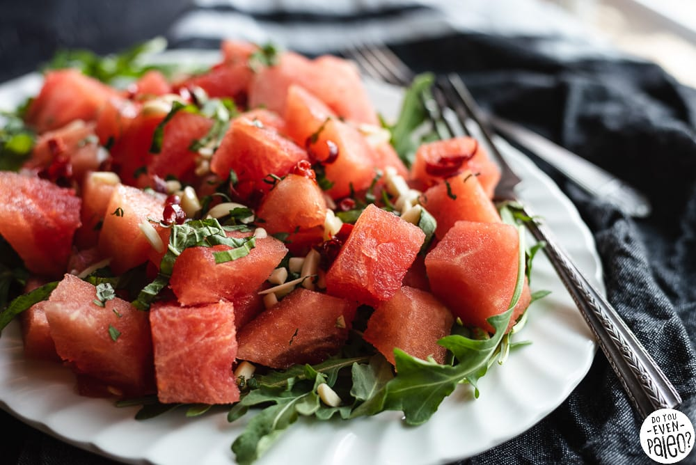 Watermelon Arugula Salad on a white plate beside forks