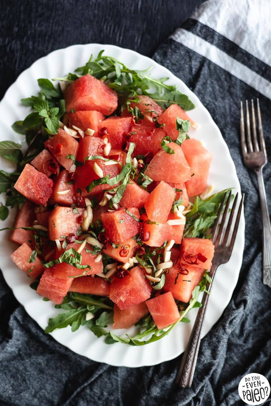 Watermelon Arugula Salad garnished with herbs and almonds on a white oval plate with two forks on a dark background.