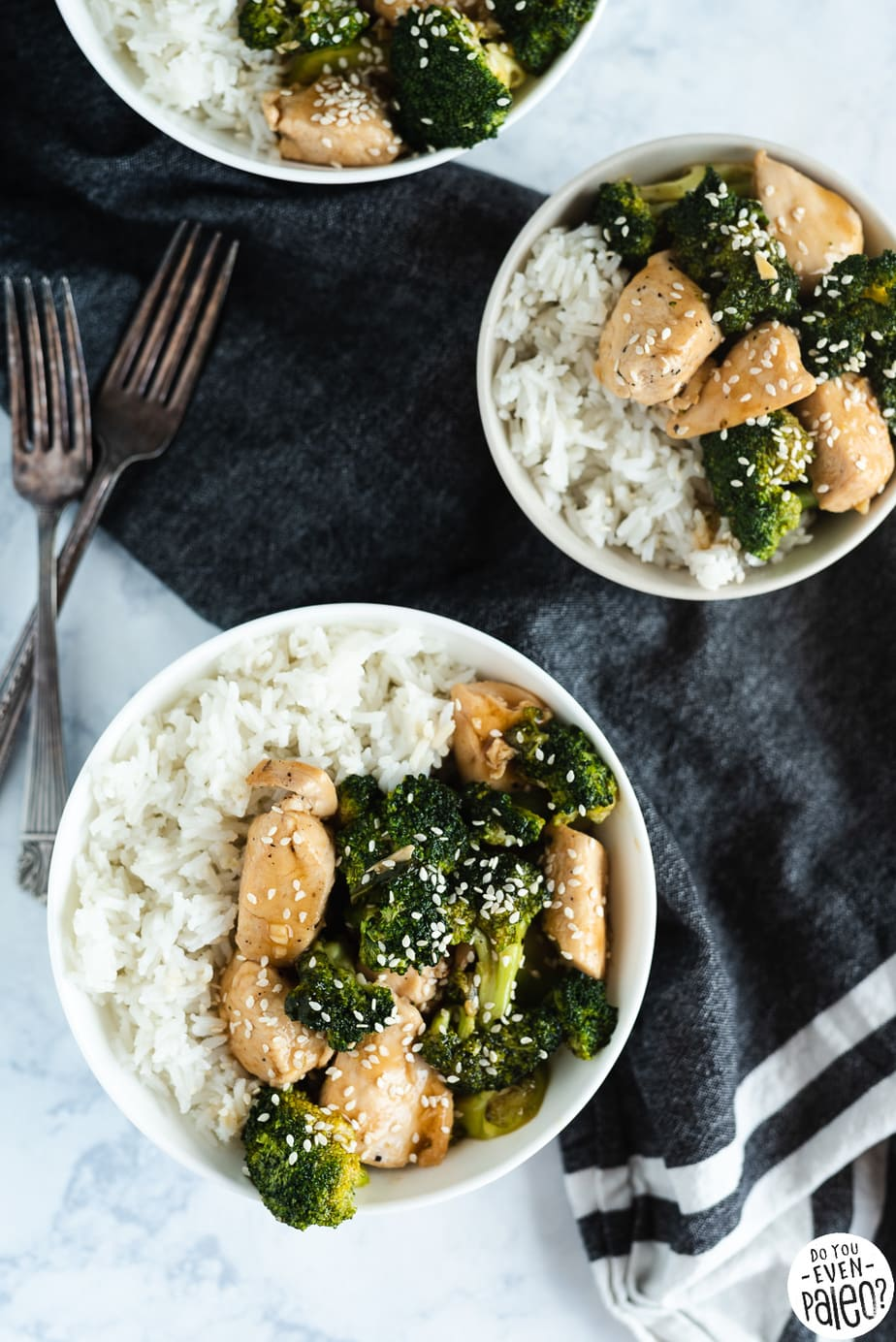 Three bowls of Quick & Easy Chicken & Broccoli Stir Fry Recipe ingredients with a dark napkin on a marble background by DoYouEvenPaleo.net