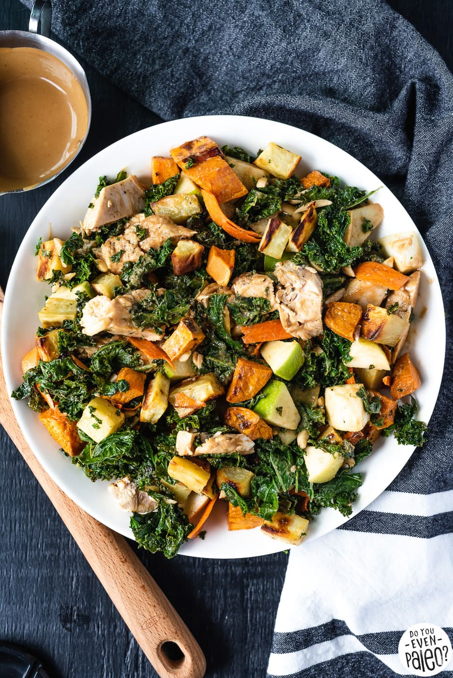 Warm Kale, Chicken, Apple, and Sweet Potato Salad on a white plate with a wooden spoon and dark linens by DoYouEvenPaleo.net