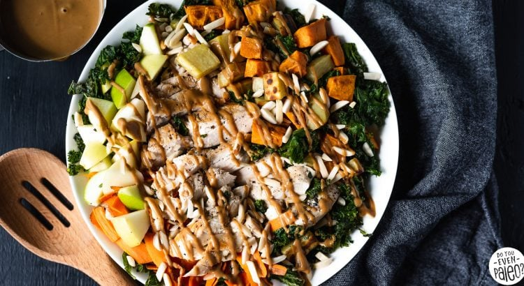 Warm Kale Apple Sweet Potato Salad Recipe on a white plate with a wooden spoon and dark linens by DoYouEvenPaleo.net