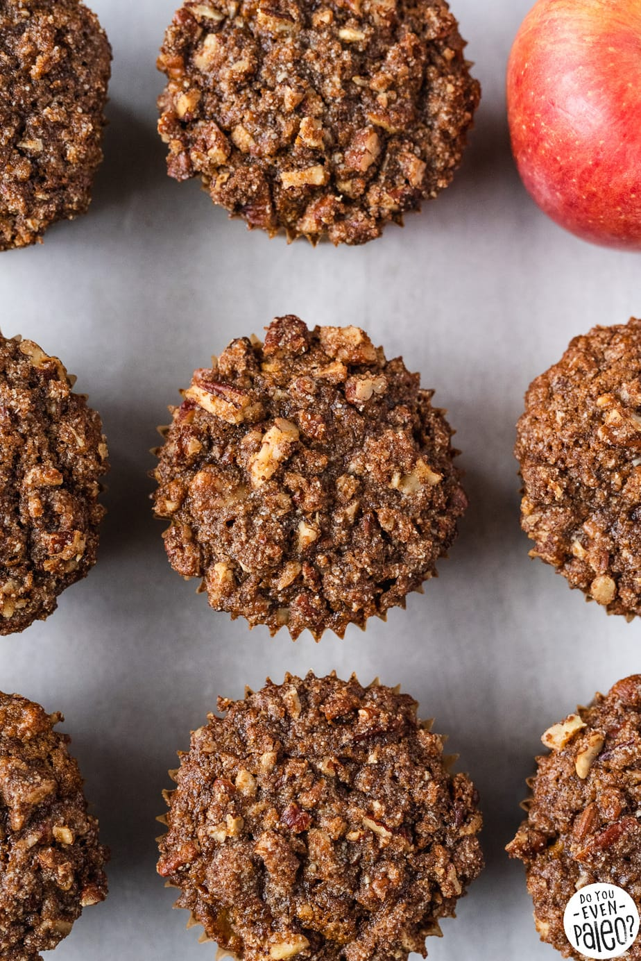 Picture of gluten free apple pecan streusel muffins recipe on a white plate with an apple on a concrete background | DoYouEvenPaleo.net