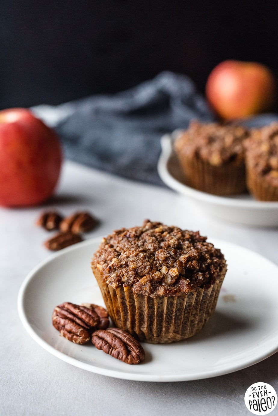 Picture of paleo apple pecan streusel muffins recipe on a white plate with pecans and an apple on a concrete background | DoYouEvenPaleo.net