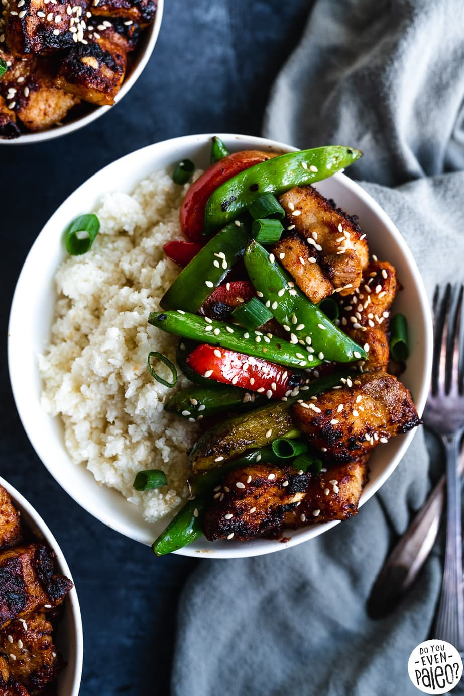 Paleo Pork Belly Stir Fry Recipe with veggies and cauliflower rice in a white bowl on a dark background by DoYouEvenPaleo.net