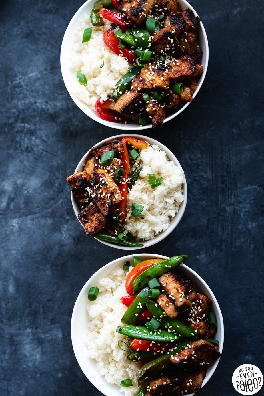 Paleo Pork Belly Stir Fry Recipe with veggies and cauliflower rice arranged in three white bowls on a dark background by DoYouEvenPaleo.net