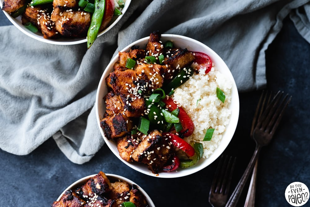 Gluten Free Pork Belly Stir Fry Recipe with veggies and cauliflower rice arranged in three white bowls on a dark background by DoYouEvenPaleo.net