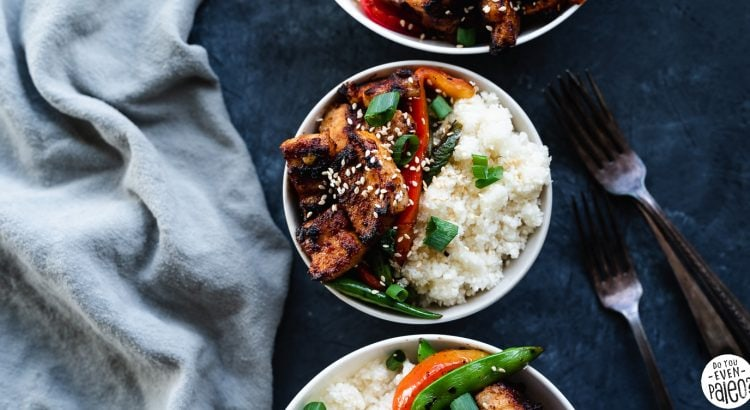 Paleo Pork Belly Stir Fry Recipe with veggies and cauliflower rice in bowls on a dark background by DoYouEvenPaleo.net