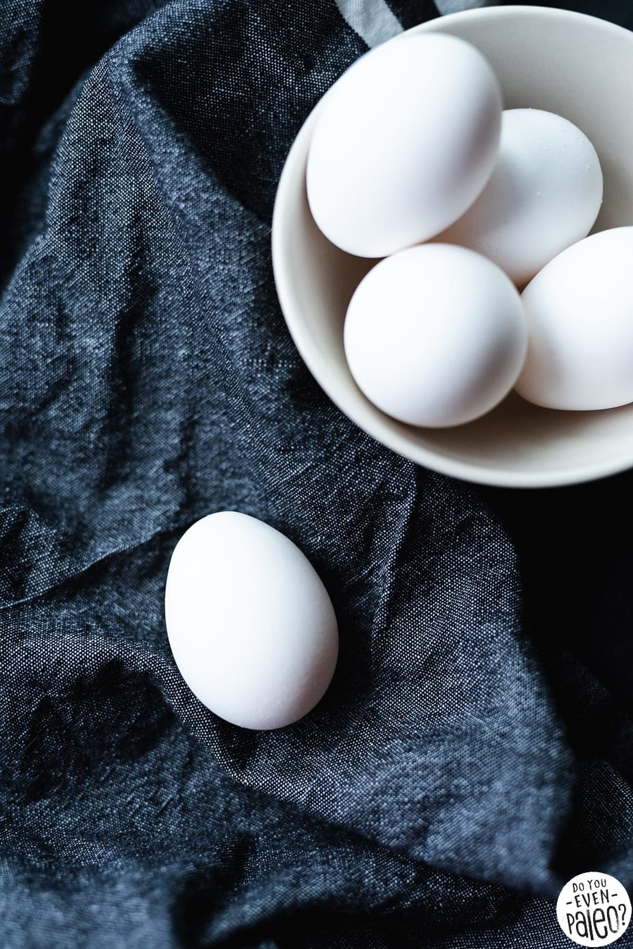 White eggs in a dish with a single egg on dark linens by DoYouEvenPaleo.net