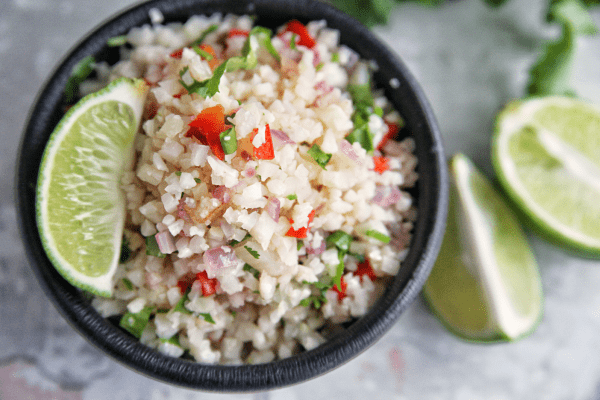 Bowl full of mexican cauliflower rice with lime garnish
