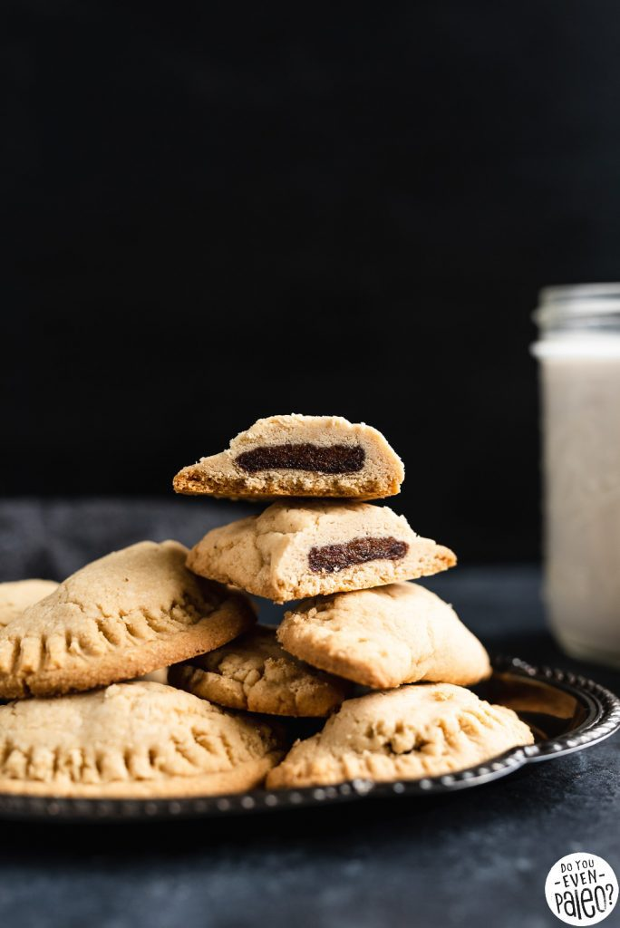 Stuffed date cookies stacked on a plate with a jar of milk in the background