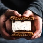 Hands holding a paleo s'mores bar with graham crackers, melted chocolate, and marshmallow