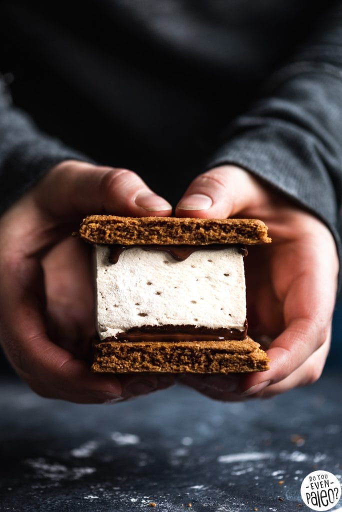 Hands holding a paleo s'mores bar with graham crackers, melted chocolate, and; Homemade ...