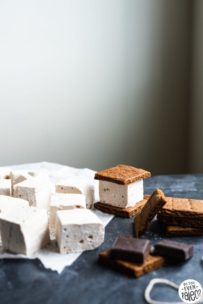 Homemade marshmallows and graham crackers being assembled into s'mores bars