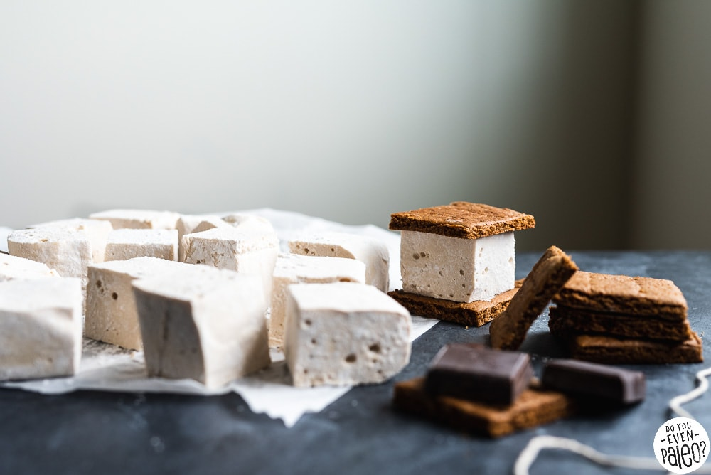 Homemade marshmallows, graham crackers, and blocks of chocolate arranged on a countertop