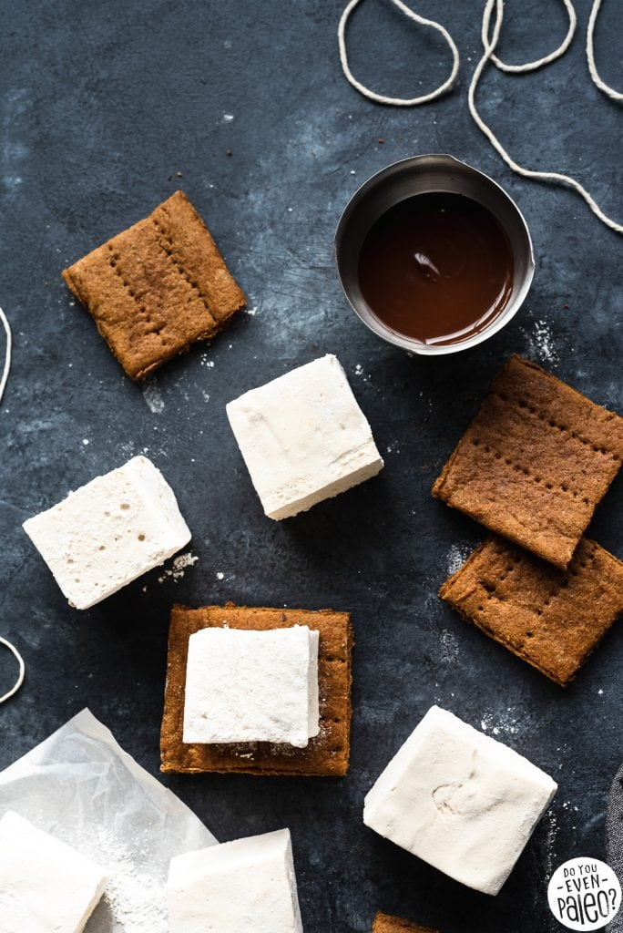 Homemade marshmallows, homemade graham crackers, and a bowl of melted chocolate on a dark background