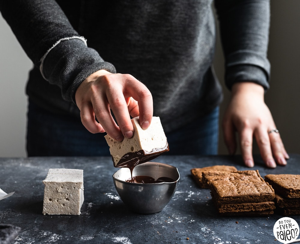 Woman dipping homemade marshmallows into a bowl of melted chocolate, with graham crackers to the side
