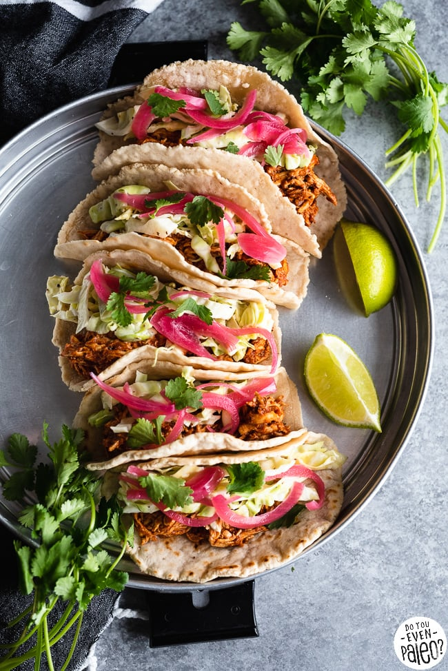 Paleo BBQ Chicken Tacos with Slaw arranged on a stainless steel tray with lime wedges