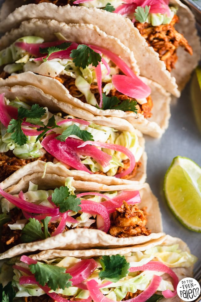 BBQ Chicken Tacos with Slaw arranged on a stainless steel tray with lime wedges