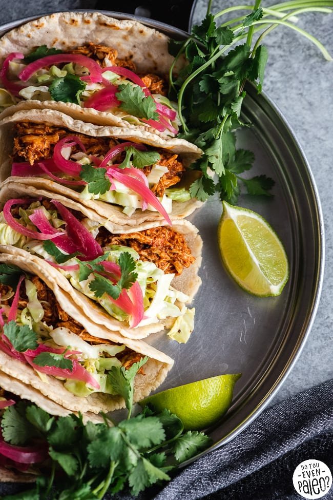 BBQ Chicken Tacos with Slaw arranged on a stainless steel tray with lime wedges and cilantro