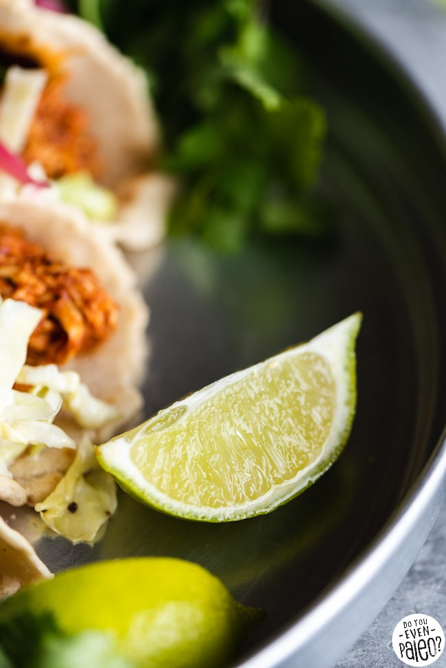 Closeup of lime next to paleo BBQ chicken tacos with coleslaw