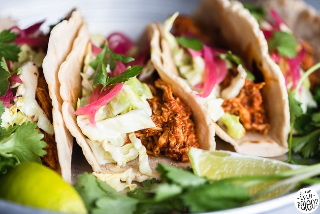 Gluten Free BBQ Chicken Tacos with Slaw arranged on a stainless steel tray with lime wedges