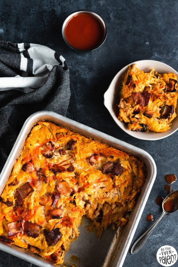 Baking pan with Whole30 Bacon Buffalo Chicken Casserole recipe on a dark background