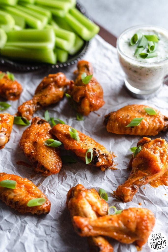 Garlic buffalo chicken wings arranged on parchment paper with a platter of celery sticks and bowl of homemade ranch dip