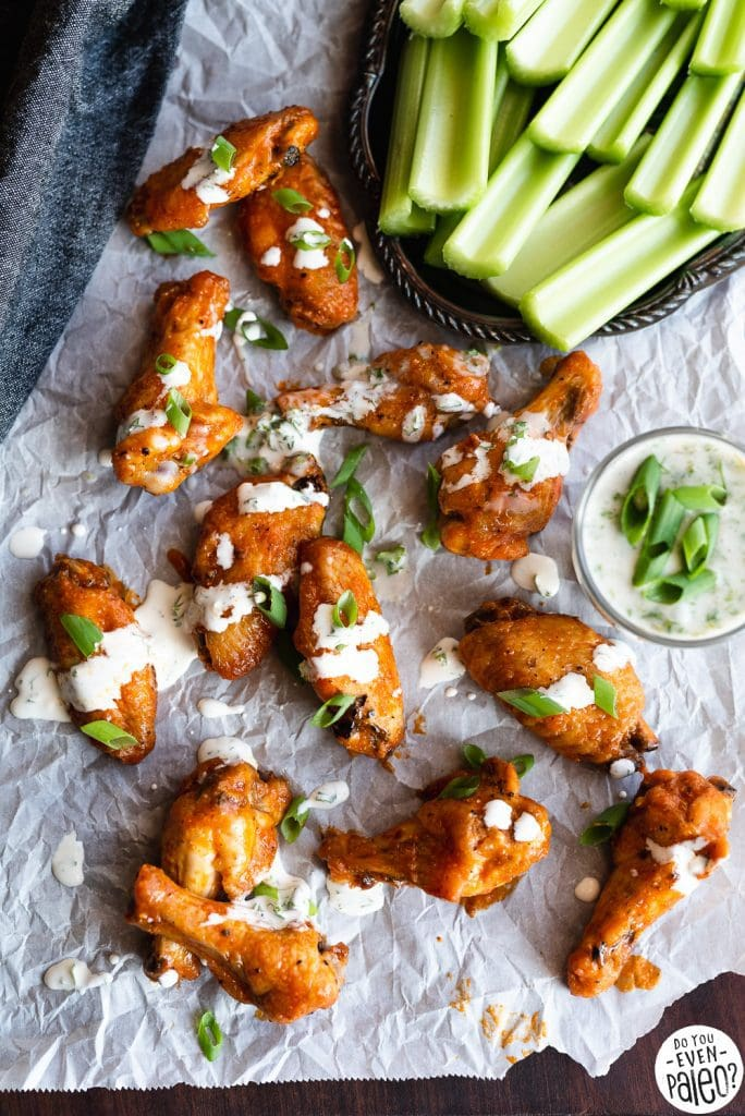 Garlic buffalo chicken wings drizzled in ranch arranged on parchment paper with a platter of celery sticks and bowl of homemade ranch dip