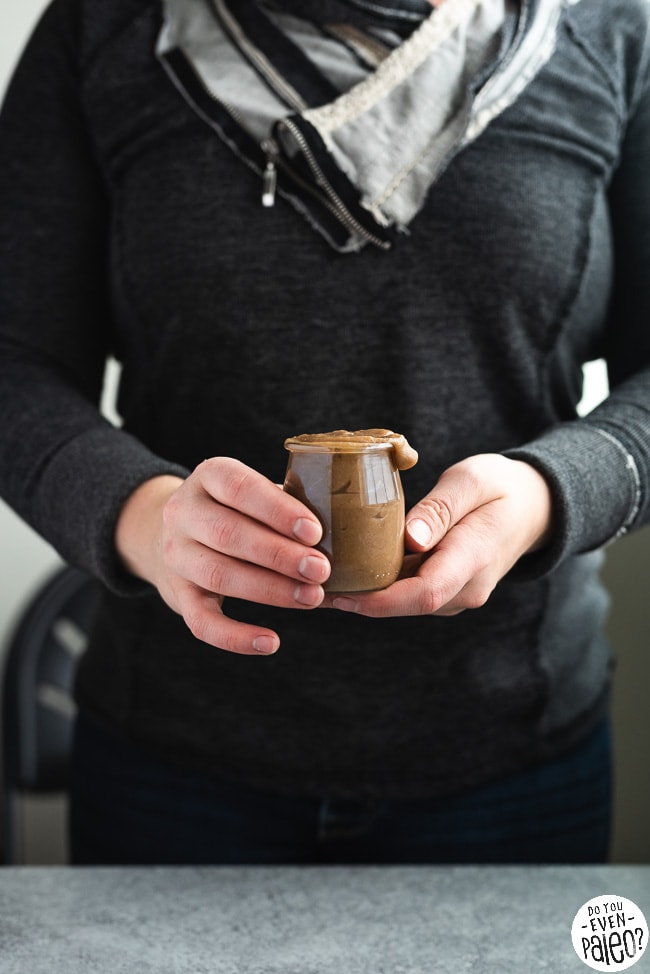 Woman holding small jar of paleo date caramel sauce