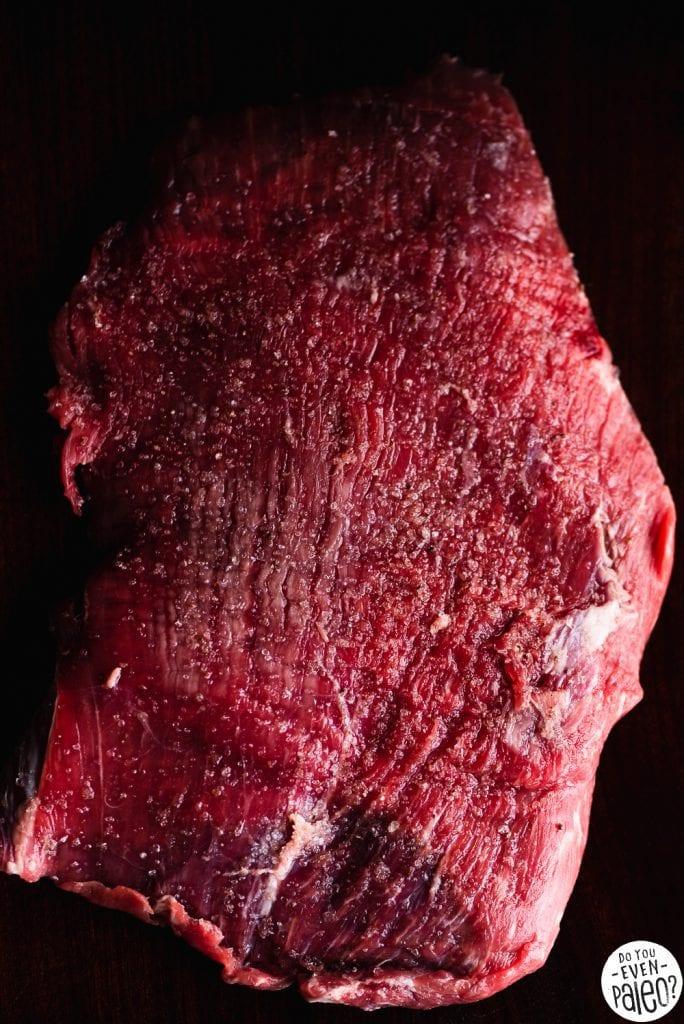 Seasoned raw flank steak on a dark background