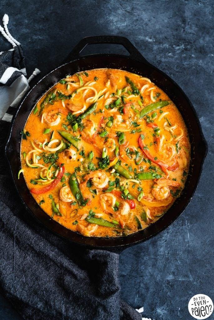 Cast iron skillet containing thai shrimp curry zucchini noodle soup