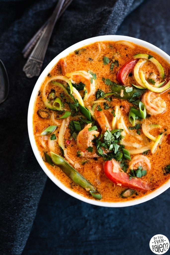 bowl containing thai shrimp curry zucchini noodle soup on a dark background