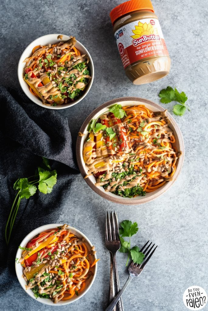 Three bowls with Thai Sweet Potato Noodles drizzled in sunbutter dressing, plus a jar of Sunbutter on a light background