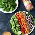 Chopped Spinach Salad and spinach arranged on plates, with a container of Sunbutter vinaigrette and a jar of Sunbutter to the side