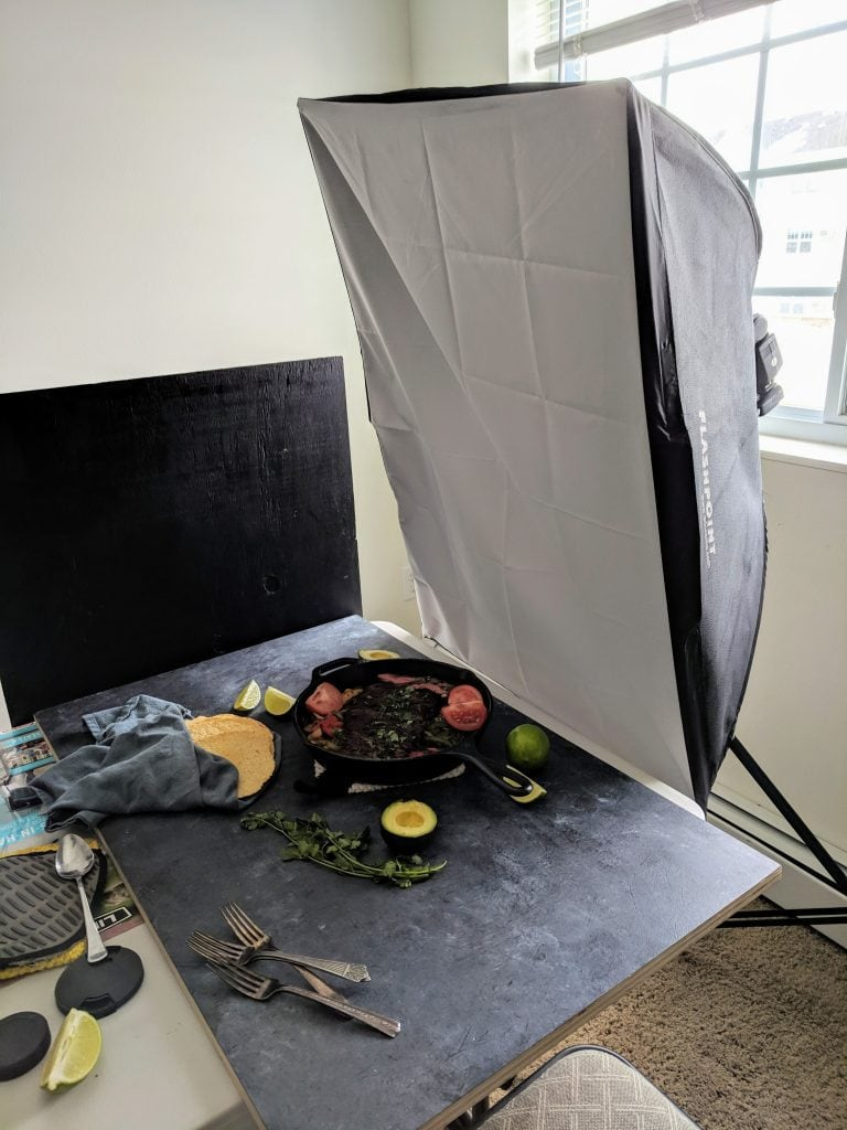 photography setup, showing skillet steak fajitas on a dark backdrop and a large softbox