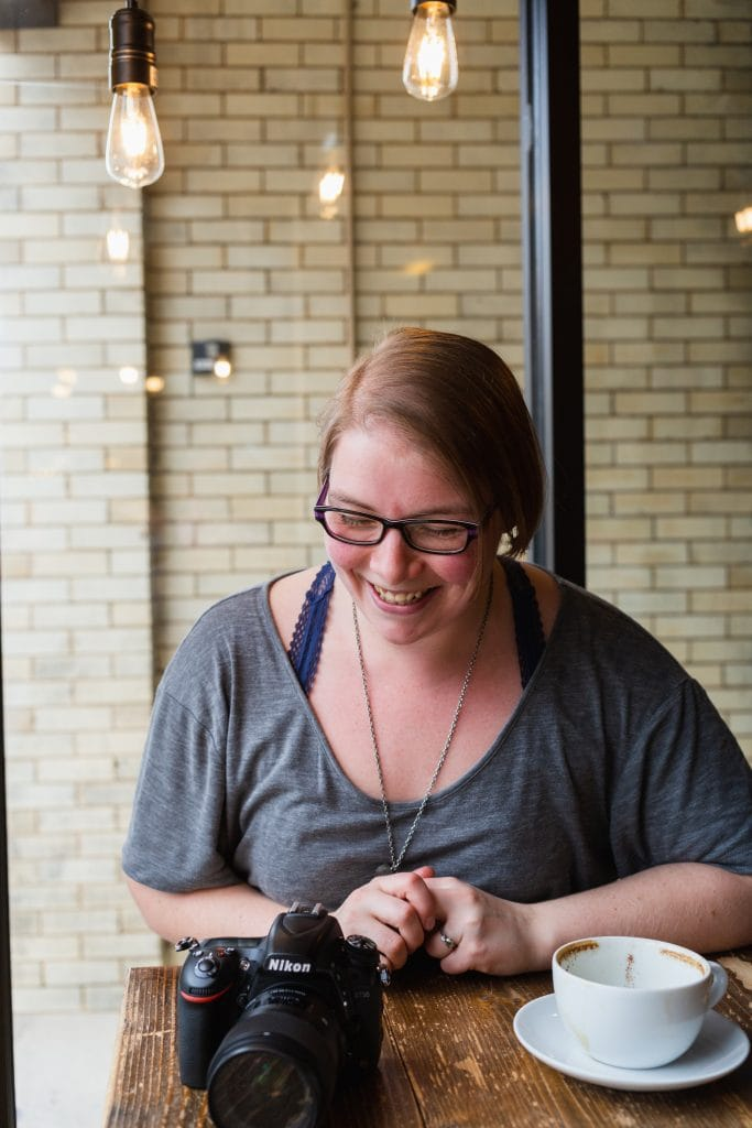 Woman laughing in a coffee shop with a cup of coffee and camera. Photo by Alecs Kay Photography