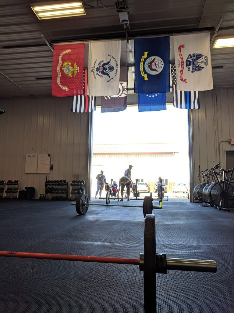 Strong Roots ND with barbells on the floor and flags hanging from the ceiling
