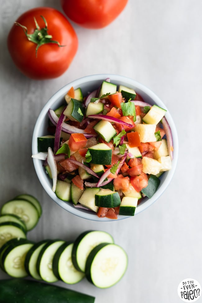Bowl filled with paleo Greek salsa surrounded by tomatoes and cucumbers