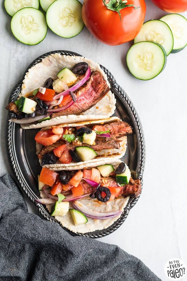 Gluten free steak tacos with Greek salsa on a small plate with cucumbers and tomatoes
