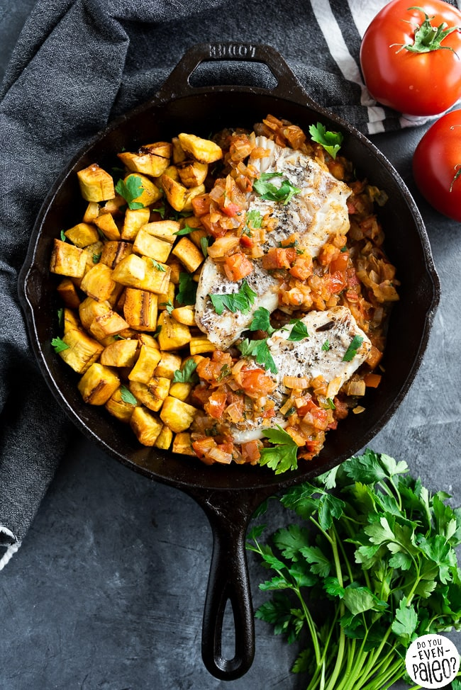 Cast iron skillet with fried plantains, grilled fish, and a tomato onion mixture