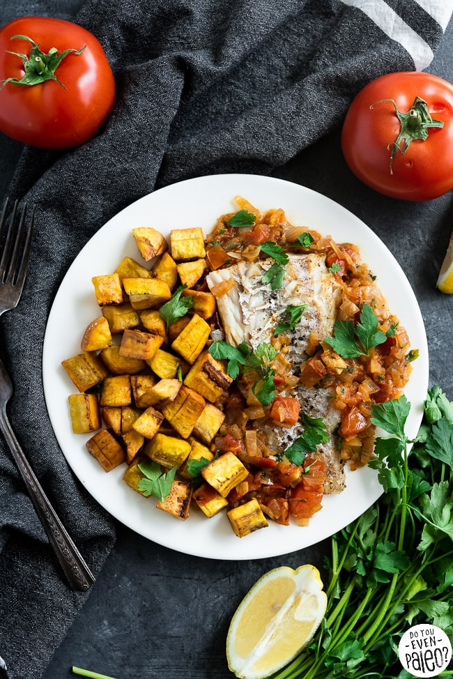 Fried plantains and grilled fish with a tomato onion sauce on a white plate