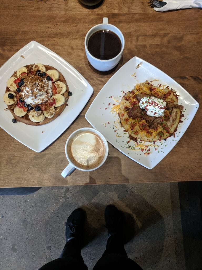 two plates with waffles and two cups of coffee on a wood table