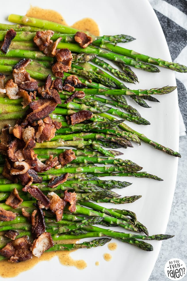 Roasted asparagus with bacon and maple mustard vinaigrette on a serving plate