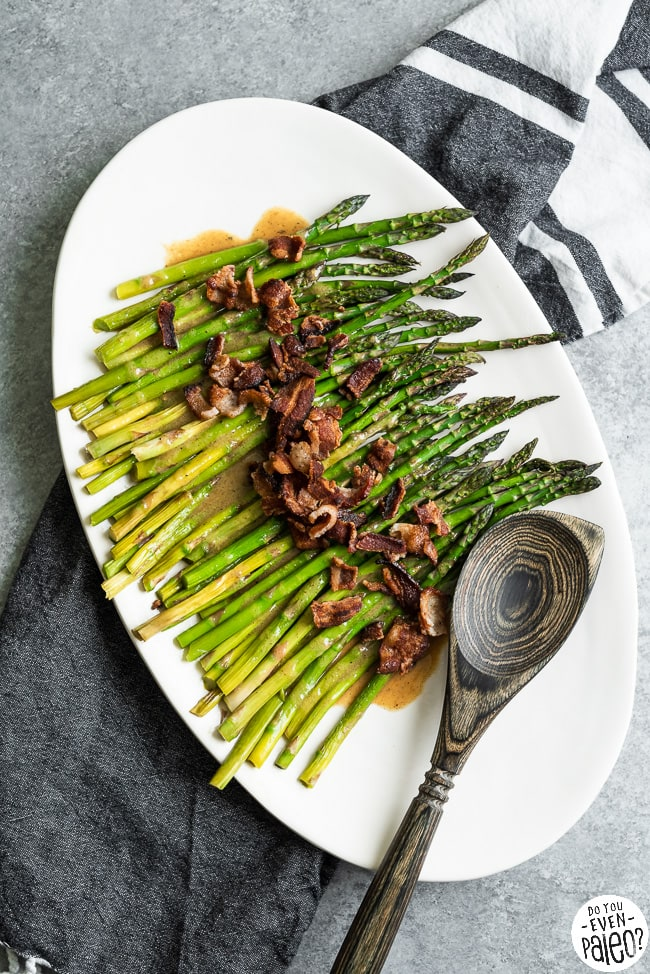 Serving tray with paleo roasted asparagus topped with crumbled bacon and maple vinaigrette